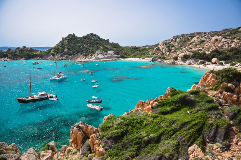 Sail boats in the Mediterranean, calm sea surrounded by rocky landscape on a Sailsquare sailing holiday