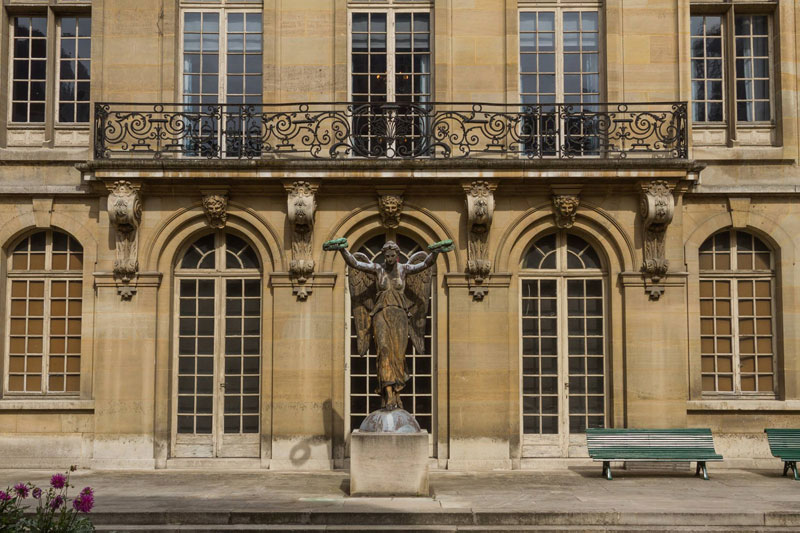 Stone facade of a grand mansion house in Paris with wrought iron balcony, now Musee Carnavalet