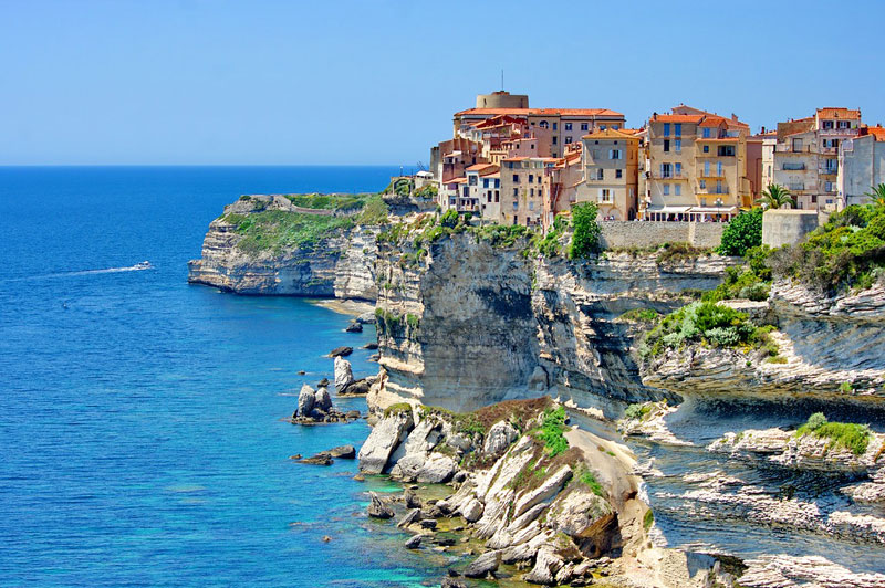 A colourful town built on a rocky island seen from a cruise ship in the Mediterranean Sea
