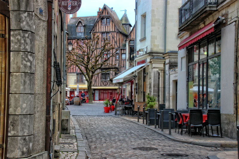Cobbled street with tables and chairs on the pavement for al fresco dining in Tours, Loire Valley