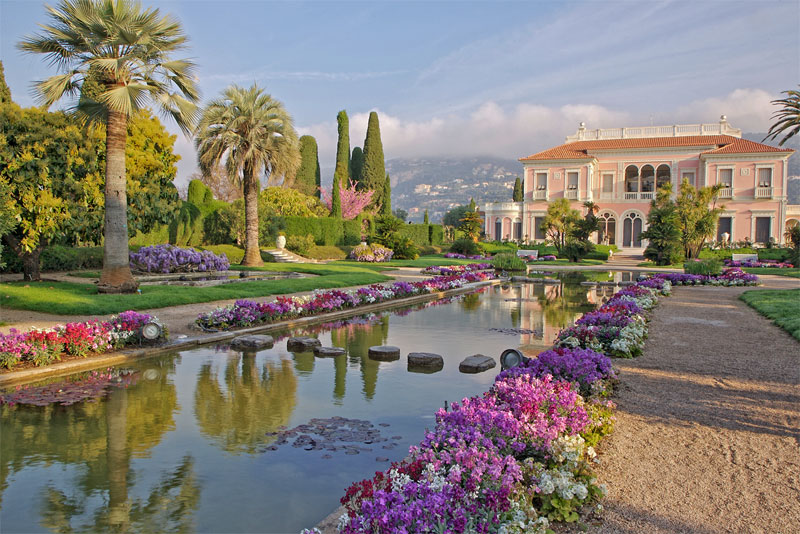 A formal garden filled with pink flowers and palm trees, mountains in the background near Nice, southern France
