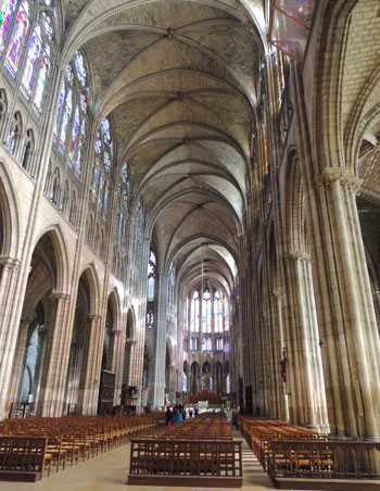 Nave of Saint Denis Church, Paris, very high ceiling, stained glass windows casting coloured light over the light stone walls