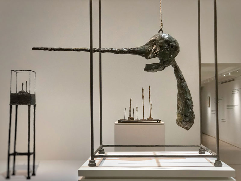 Sculpture by Alberto Giacometti, round black head with a very long pointed nose hangs from the ceiling