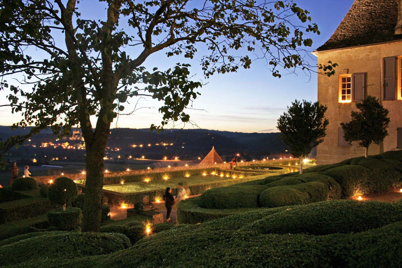 Candlelit gardens of filled with thousands of topiary trees on a hill