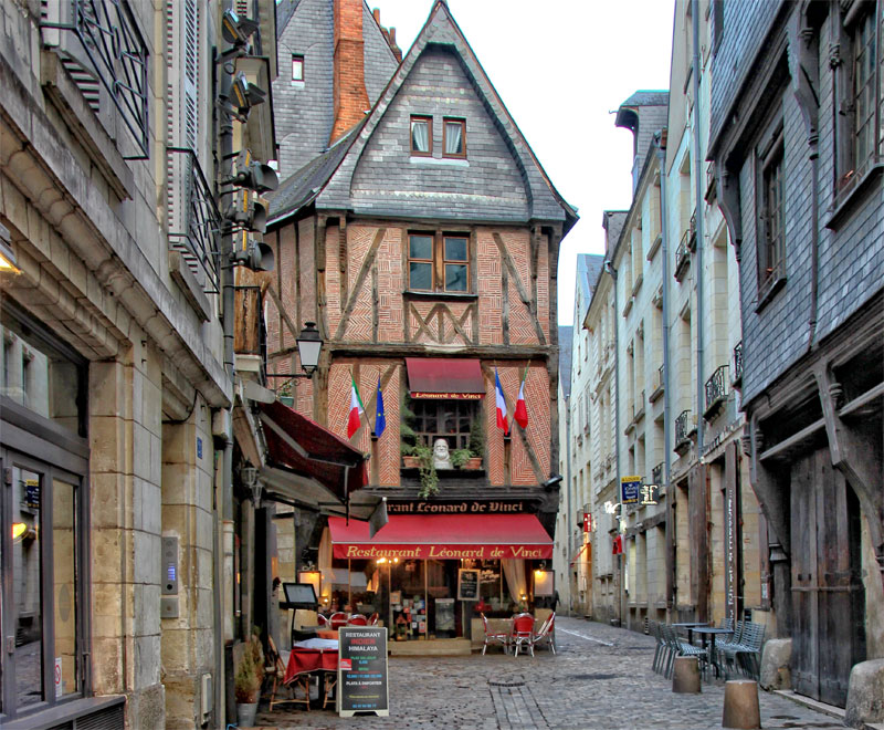 Historic cobbled street in Tours with many half timbered houses and colourful shops and restaurants
