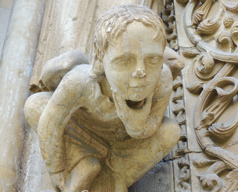 Ancient stone carving of Saint Denis, carrying his own head as the legend goes at the Basilica of Saint-Denis, Paris