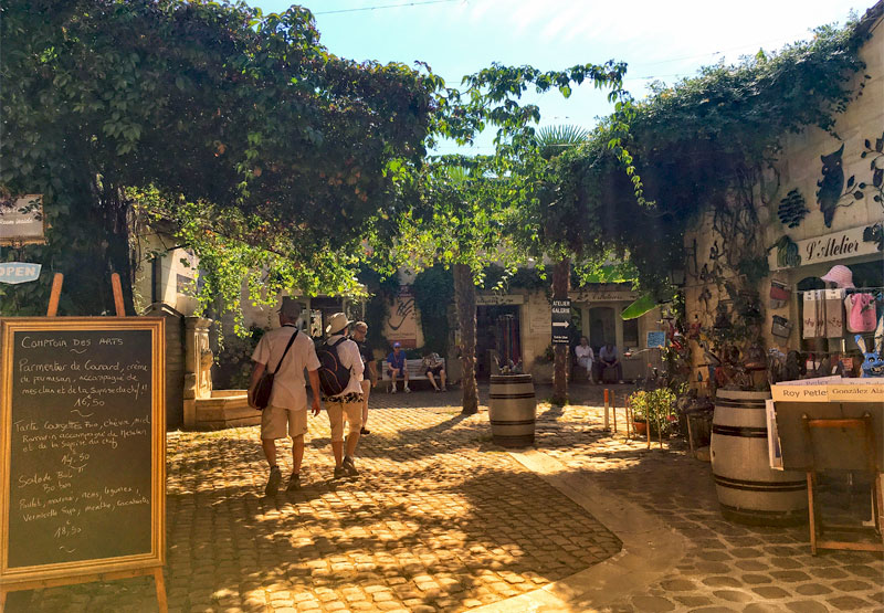 Vines growing across a pretty cobbled square in Saint-Emilion cast shade over diners