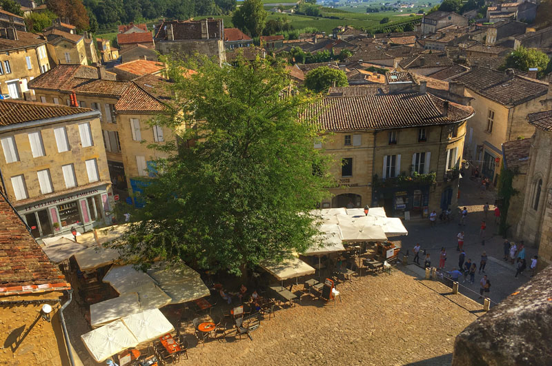 View over the town of Saint Emilion and its main square, yellow stone buildings, and tables on terraces