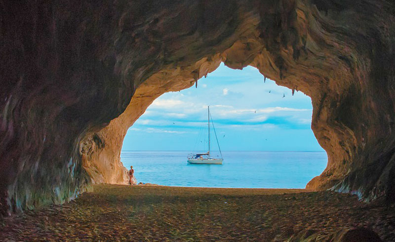 Azure blue waters of the Mediterranean Sea viewed from a secret cave, a boat bobs close to the shore