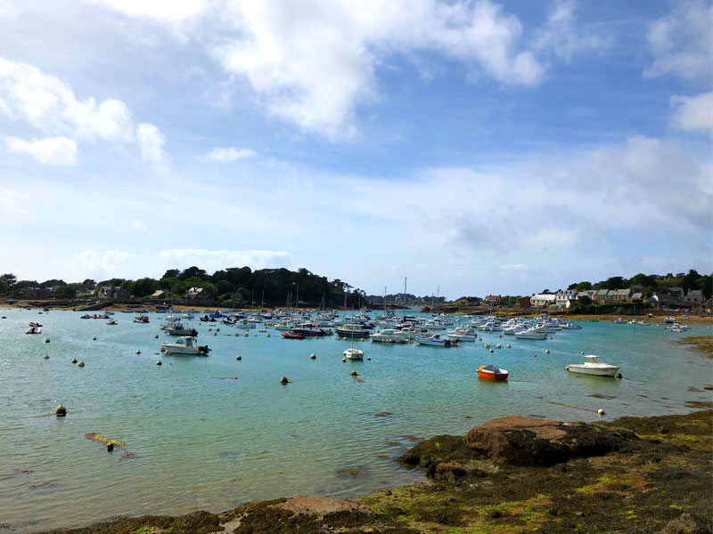Boats bobbing about in the tranquil bay of Ploumanac'h Brittany with its clear blue waters