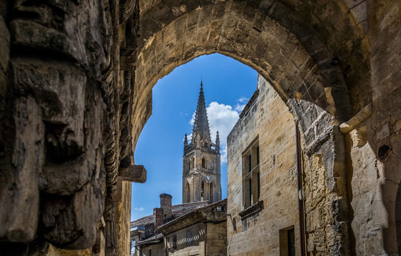 View of an ancient church through a rocky archway in the medieval town of Saint-Emilion