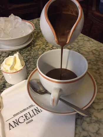 Hot chocolate being poured from a jug at Angelina tea room in Paris
