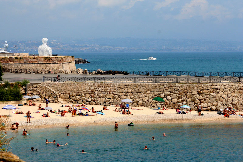 People sunbathing on a sandy beach on a sunny day in Antibes, southern France
