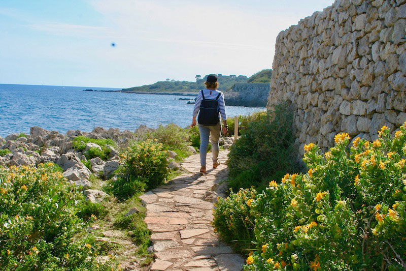 Woman walking on a hiking trail alongside the Mediterranean Sea in Antibes, southern France