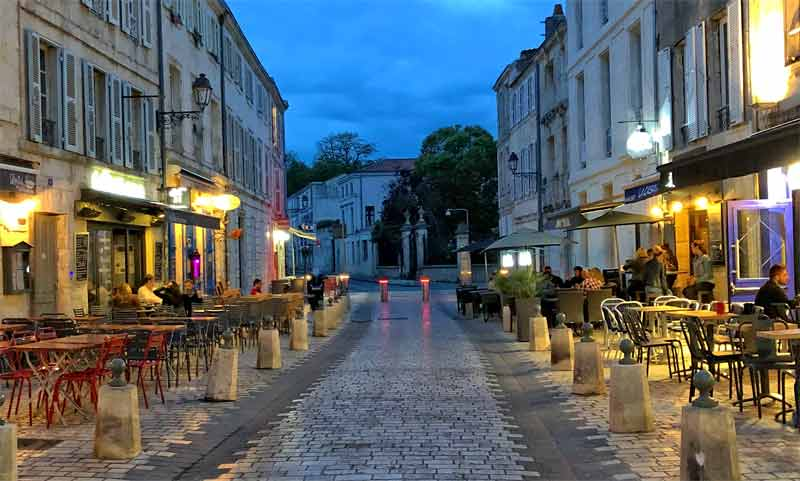 Cobbled street lined with restaurants at dusk in la Rochelle