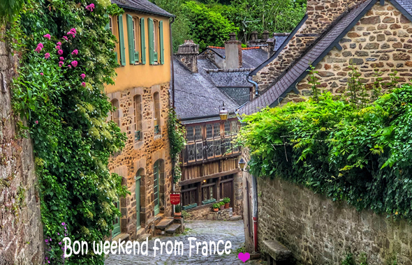 Hilly cobbled street, lined with ancient houses dripping with flowers in the town of Dinan in Brittany,