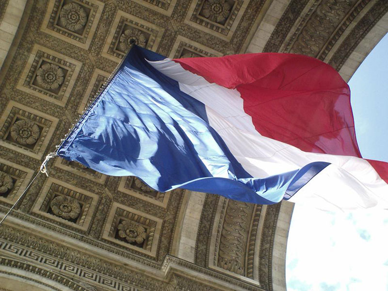 Blue, white and red flag of France at the Arc de Triomphe, Paris