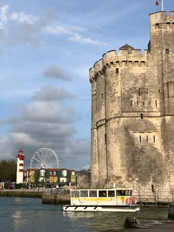 Small pleasure boat passes before the grand old tower of La Rochelle