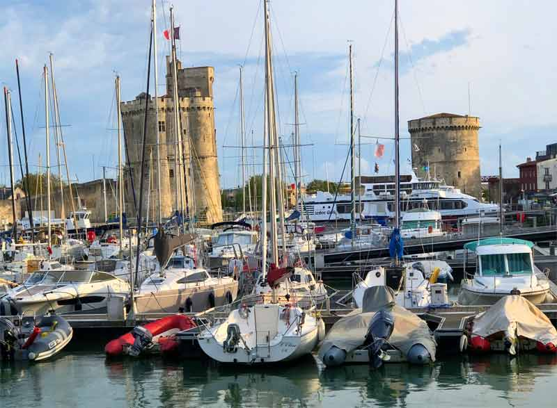 Boats in the port of La Rochelle, tall stone towers in the background