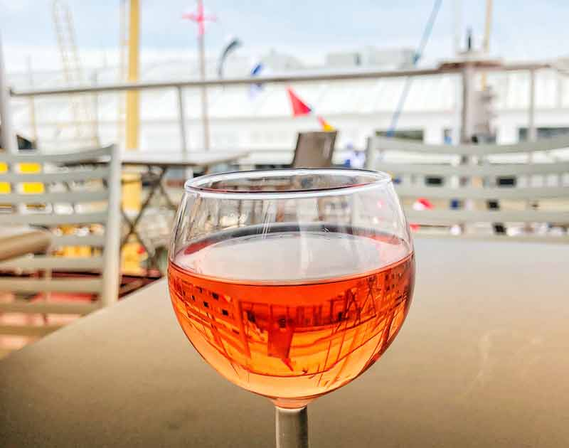 Glass of wine reflects the flags of a boat