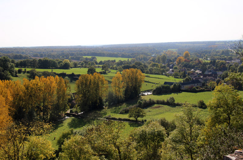Grassy valleys peppered with trees and tiny hamlets in Mayenne, France