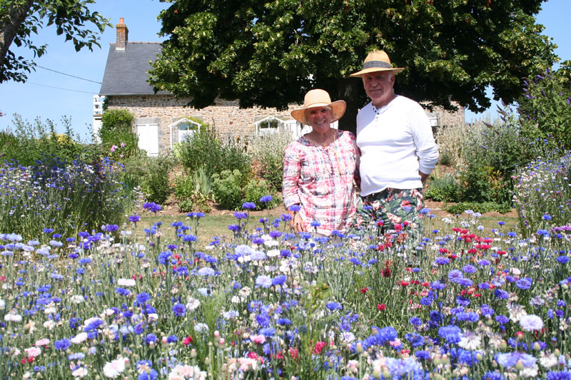 Couple standing in their garden full of flowers, pretty stone cottage in background, Mayenne France