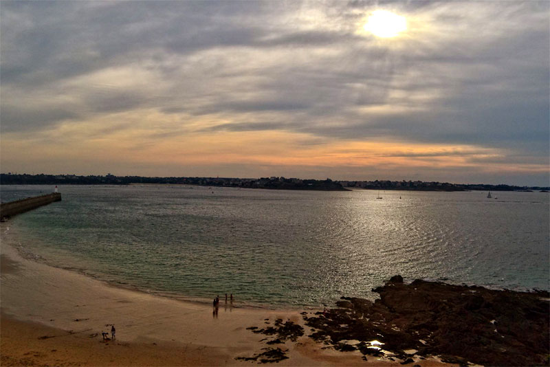 Saint Malo beach as the sun sets, the water very tranquil, the sand glowing gold in the evening sunlight