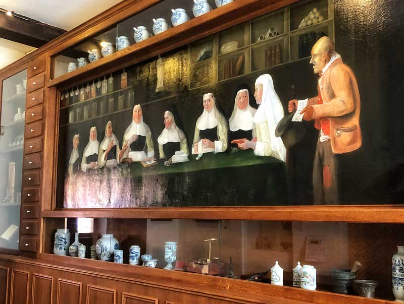 Painting of nuns giving money medicine to a poor man in middle ages at Hospice de la Comtesse, Lille