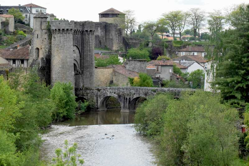 Castle walls and towers astride a bridge and ancient gate into Parthenay, a town in Deux Sevres