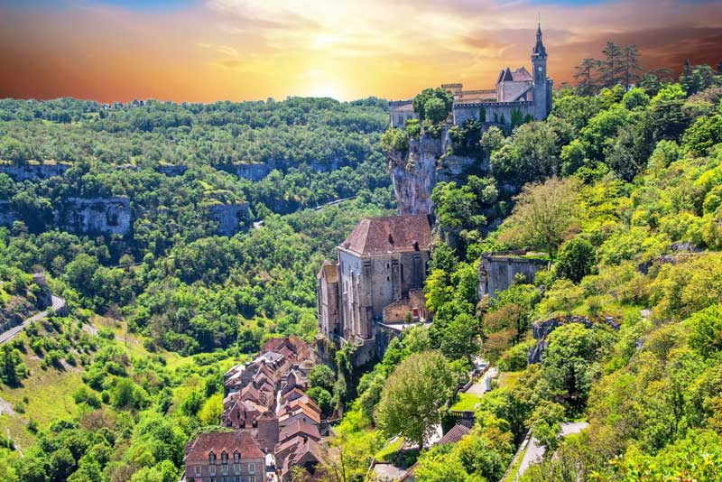 Church on top of a hill, houses on its slopes under a dramatic sunset in Rocamadour, Dordogne