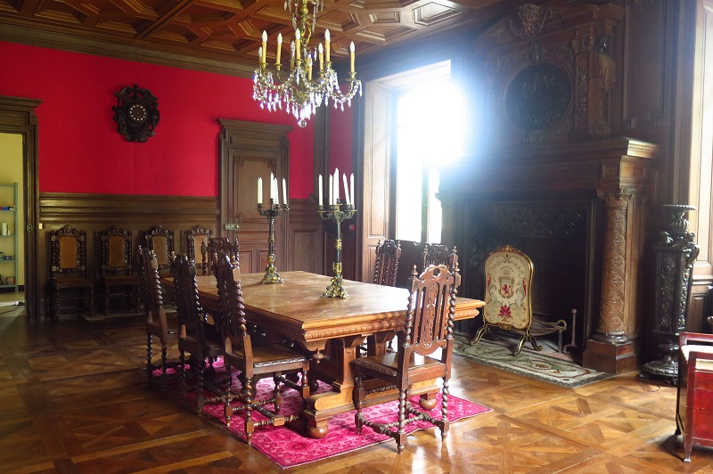 Wood paneled salon with chandelier and oak furniture in a castle in France