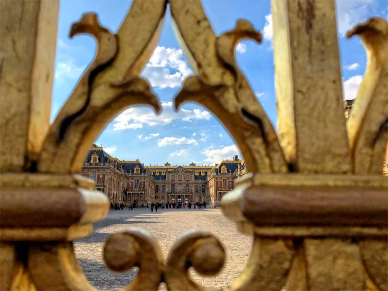 Peeping through the golden gates of the Chateau of Versailles to see the castle