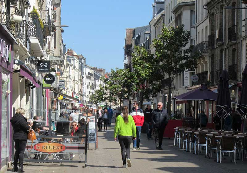 Street in the old town of Dieppe in Normandy lined with tall buildings and many shops