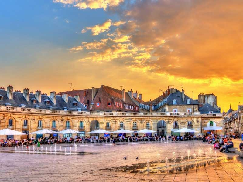 Large paved square known as Place de la Liberation in Dijon lined with restaurants and shops
