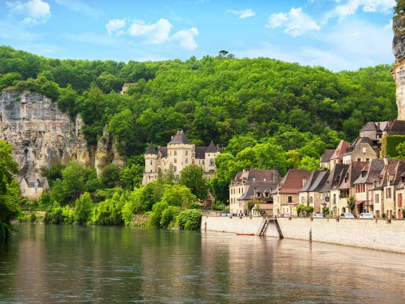 Castle and houses alongside the river Dordogne, a backdrop of forested cliffs under a sunny sky