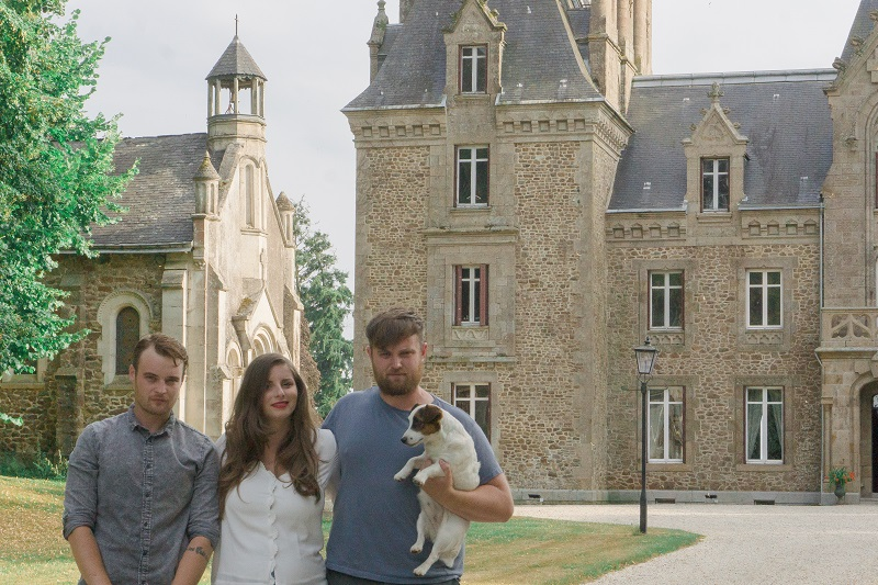 Two men and a woman with a small dog in front of a beautiful castle