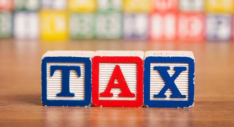 Print blocks spelling the word tax in red, white and blue