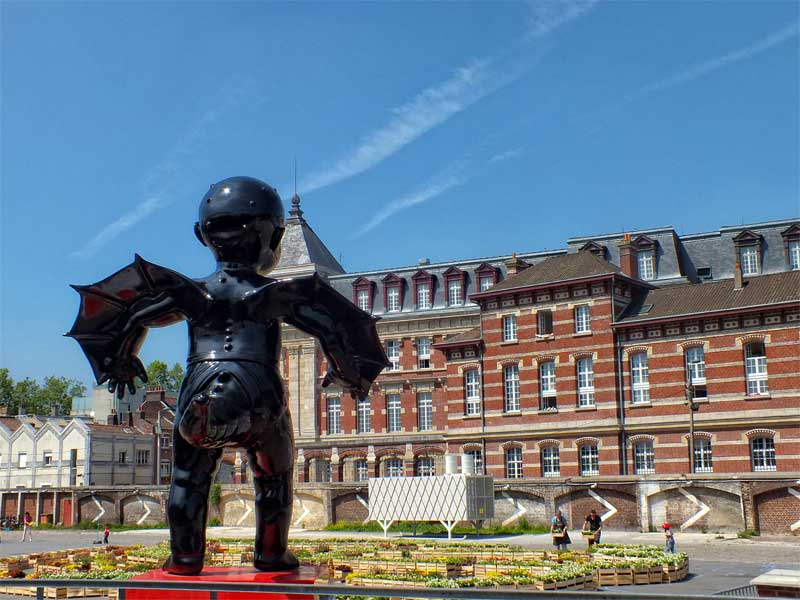 Statue of a giant baby with wings and a tail, artwork at Gare Saint Sauveur, Lille
