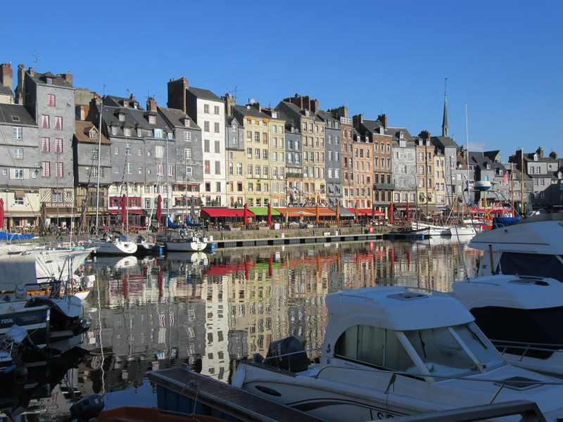 The old port of Honfleur in Normandy, small boats, tall ancient buildings surround it, colourful awnings on shops,