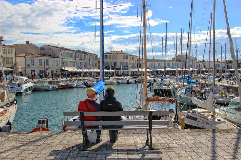 Man and woman sit on a bench enjoying the view of the port of Saint Martin, Ile de Re