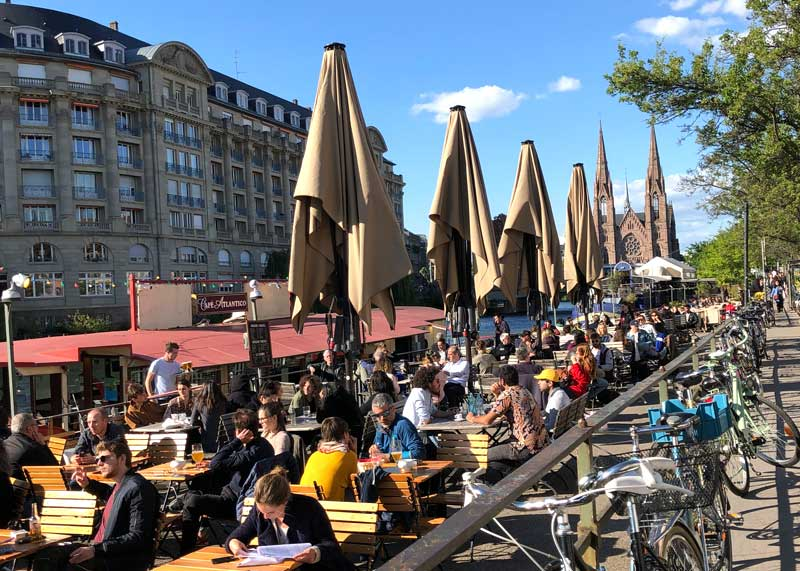 Lots of people sitting at the Quai des Pecheurs enjoying a drink in the sun in Strasbourg