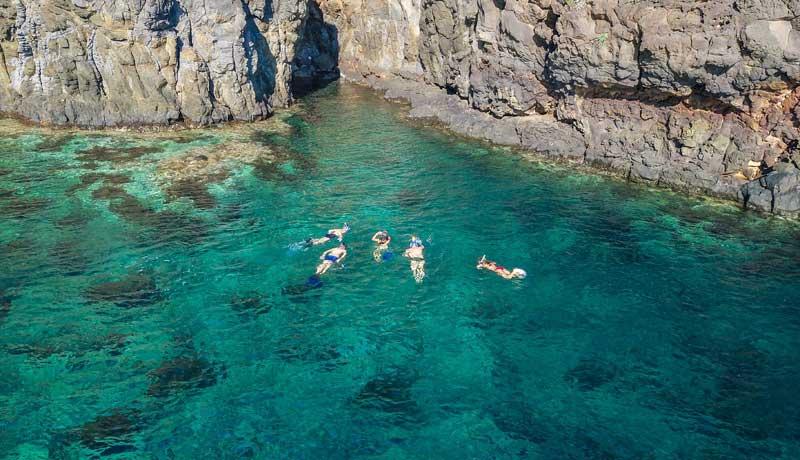 People swimming in a secluded bay in France