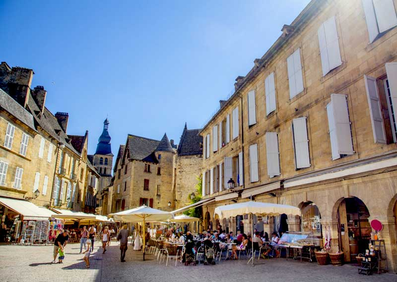 Cobbled street in medieval town of Sarlat, Dordogne, restaurants with outdoor seating