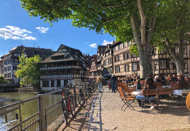 Cobbled street alongside a river in Strasbourg, half timbered houses and people sitting at a restaurant