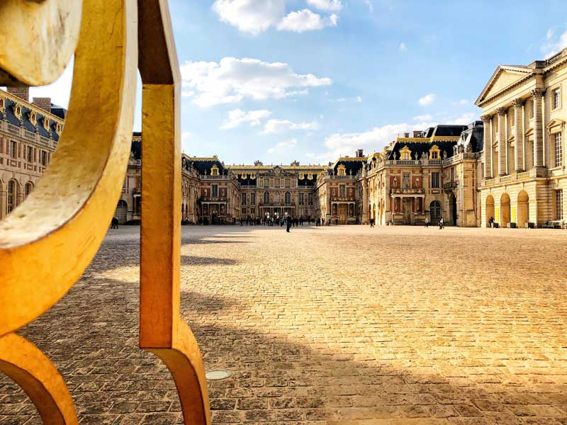 Open, golden gate, leading to the Chateau of Versailles at the end of a very long courtyard
