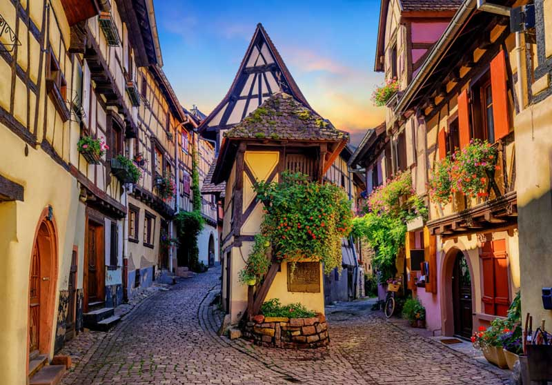 Narrow cobbled street lined with colourful half-timbered houses in village of Eguisheim, Alsace
