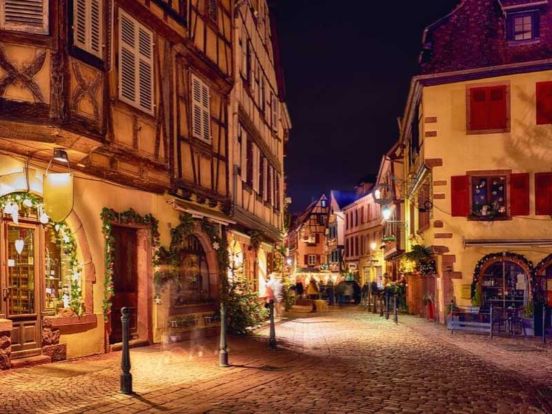 Pretty street in Alsace, shop windows lit up for Christmas at night, no people around