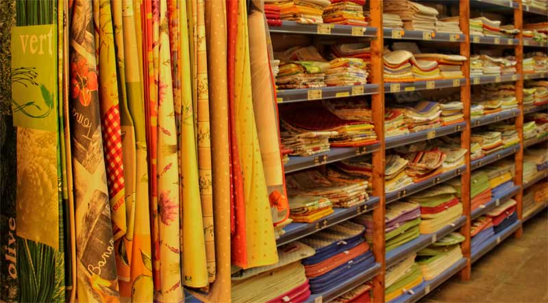 Storage shelves full of folded tablecloths in bright colours