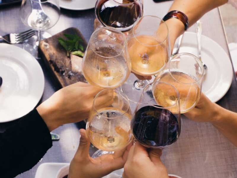 People clinking glasses of wine together in celebration