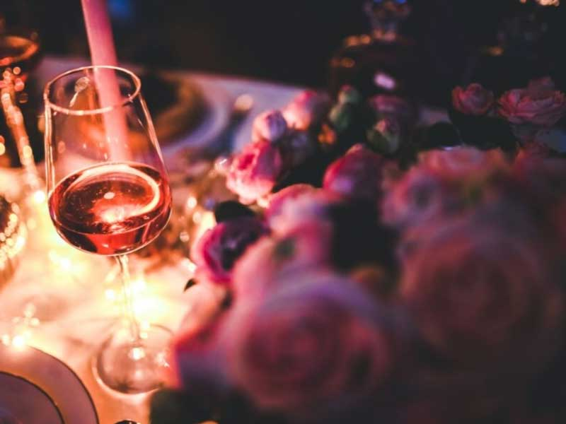 Glass of wine and a bunch of roses by candlight